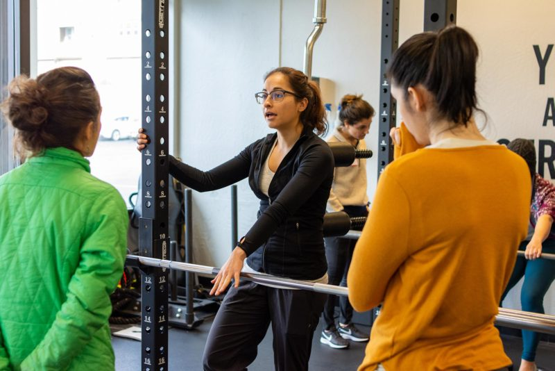 Coach Lucy Hendricks holding onto barbell and squat rack lecturing two women at The Human Matrix in Scotts Valley, California